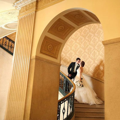 Bride and groom kissing on a staircase at the Cincinnati Club